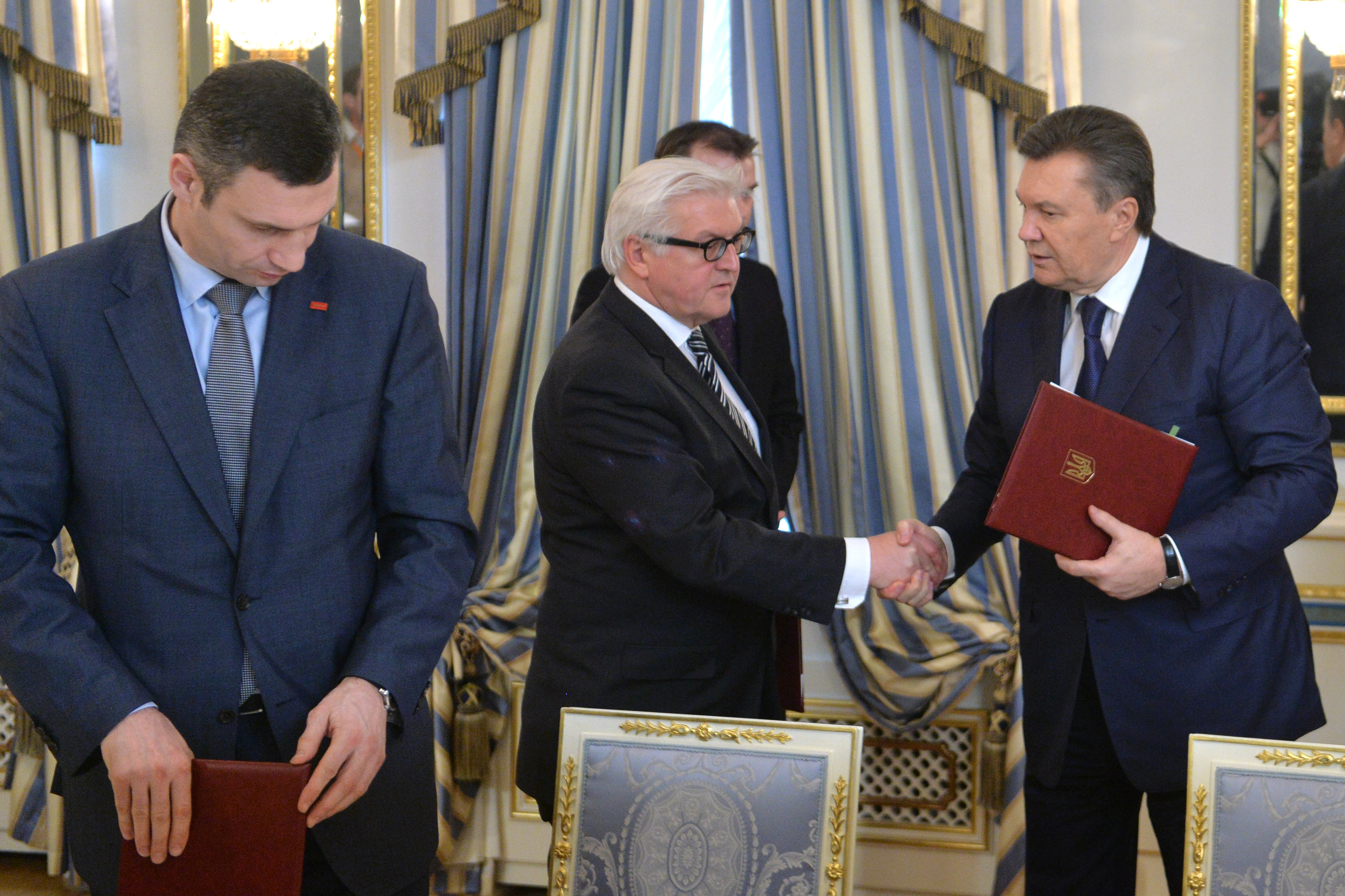 German Foreign Affairs minister Frank-Walter Steinmeier (C) and Ukrainian President Viktor Yanukovych (R) shake hands as head of Vitali Klitschko, one of Maidan's leaders, looks on after the signing of what was thought to be a compromise deal in Kiev on February 21, 2014