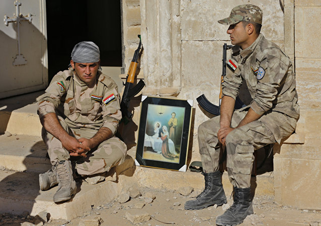 Iraqi Christian soldiers from the Nineveh Plain Protection Unit, sit next to a poster showing the Virgin Mary and Jesus Christ outside St. Addai church which was damaged by Islamic State fighters during their occupation of Keramlis village, less than 18 miles, 29 kilometers, southeast of Mosul, Iraq, Sunday Nov. 13, 2016