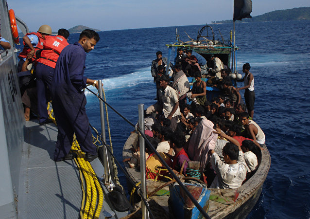Members of the Indian coastguard rescue illegal Bangladeshi migrants in their trawler after they were sighted by the Coast Guard Aircraft off Chidiyatapu Island in the southern Andaman Islands on January 8, 2009