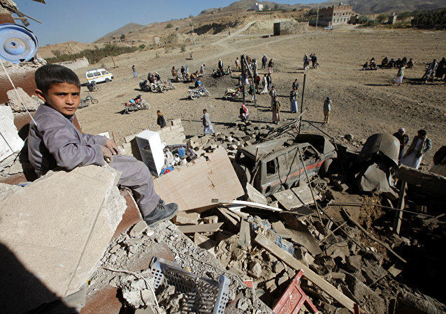 A boy looks at the camera as he sits on the wreckage of a house destroyed by a Saudi-led air strike on the outskirts of Sanaa, Yemen, November 13, 2016