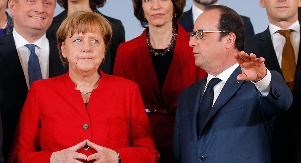 German Chancellor Angela Merkel (L) and French President Francois Hollande talk as they pose with ministers for a family picture during a joint Franco-German cabinet meeting in Metz, France, April 7, 2016.
