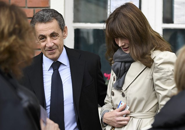 Nicolas Sarkozy (L), former French president and candidate for the French conservative presidential primary, and his wife Carla Bruni-Sarkozy speak to a women outside a polling station in the first round of the French center-right presidential primary election vote in Paris, France, November 20, 2016.