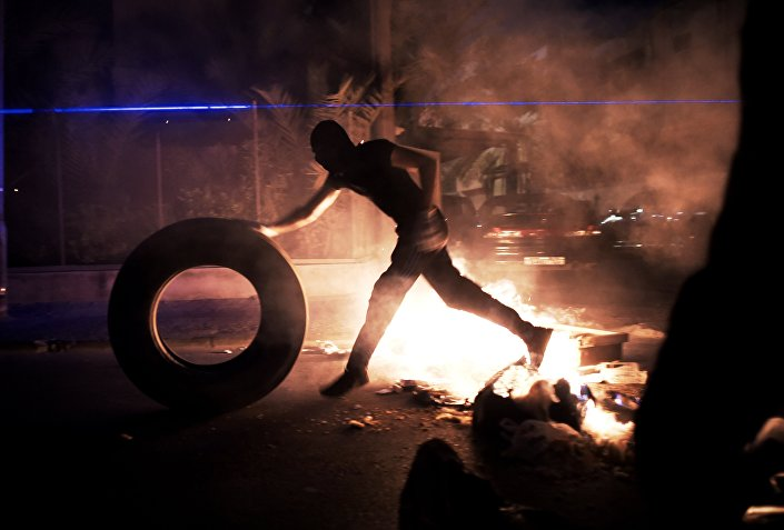 A Bahraini protester puts tyre in fire during clashes between protesters and riot police following a protest to demand more rights and against the ruling regime, late on July 10, 2014 in the village of Sanabis, west of Manama.