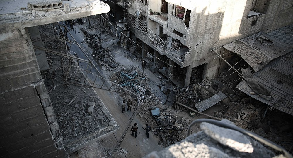 Syrians walk on a heavily damaged street on November 22, 2016, in the rebel-held town of Douma, on the eastern outskirts of the capital Damascus