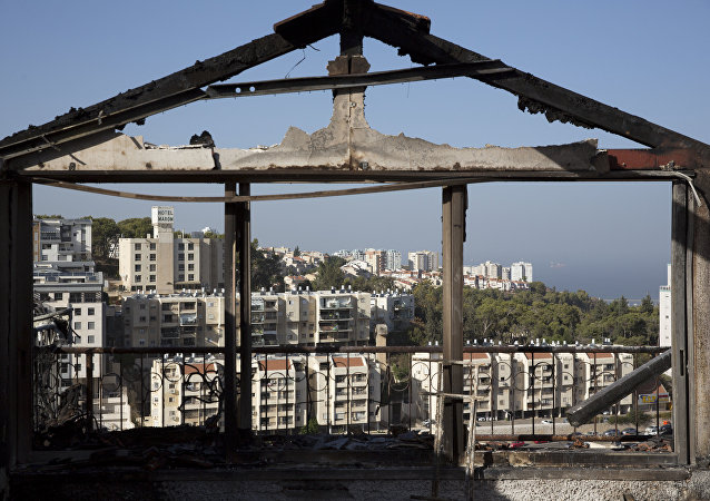 The Mediterranean sea and parts of the city can bee sen through a burned house following wildfires in Haifa, Israel, Friday, Nov. 25, 2016. Israeli firefighters reined in a blaze that had spread across the country's third-largest city and forced tens of thousands of people to flee their homes, but continued to battle more than a dozen other fires around the country for the fourth day in a row.