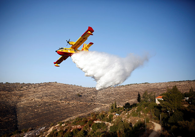 A foreign firefighting plane drops fire retardant during a wildfire, around the communal settlement of Nataf, close to Jerusalem November 26, 2016.