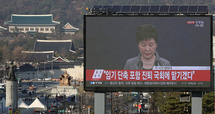 A large electronic board broadcasts a news report on South Korean President Park Geun-hye releasing a statement to the public as the Presidential Blue House (top L) is seen in the background, in central Seoul, South Korea, November 29, 2016.