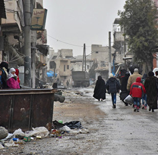 Syrian residents fleeing the eastern part of Aleppo walk through a street in Masaken Hanano, a former rebel-held district which was retaken by the regime forces last week. (File)