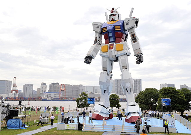 Japanese people admire an 18-metre tall statue of popular TV animation hero, Gundam, at a Tokyo park (File)