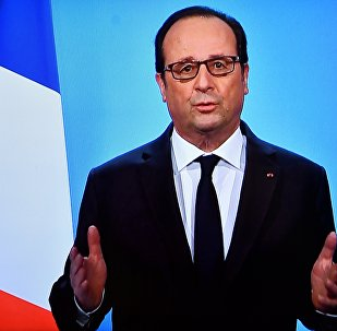 A photo taken on December 1, 2016 in Paris, shows a TV screen displaying French President Francois Hollande delivering an official statement at the Elysee Palace.