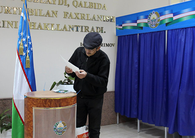 A man studies his ballot during the presidential election in Tashkent, Uzbekistan, December 4, 2016