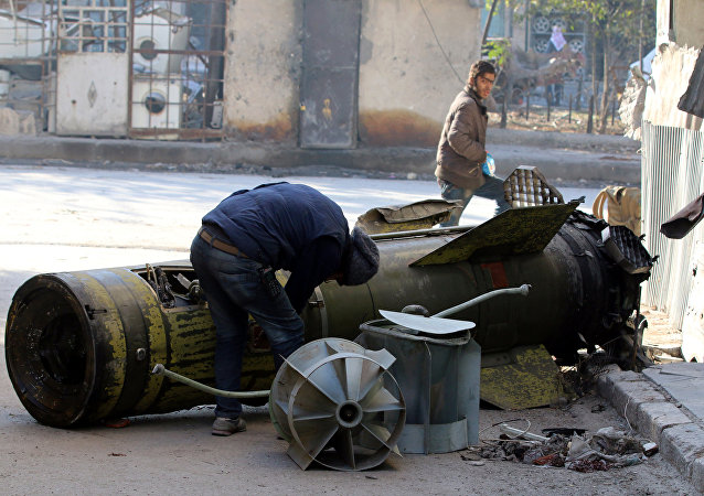 A man inspects an unexploded missile in the rebel-held besieged al-Qaterji neighbourhood of Aleppo, Syria November 28, 2016