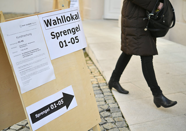 A woman past a sign showing the way to a polling station during the presidential election in Salzburg, Austria on December 4, 2016