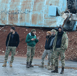 Rebel fighters stand near a damaged bus used as a barricade in the rebel-held besieged Bab al-Hadid neighbourhood of Aleppo, Syria December 2, 2016