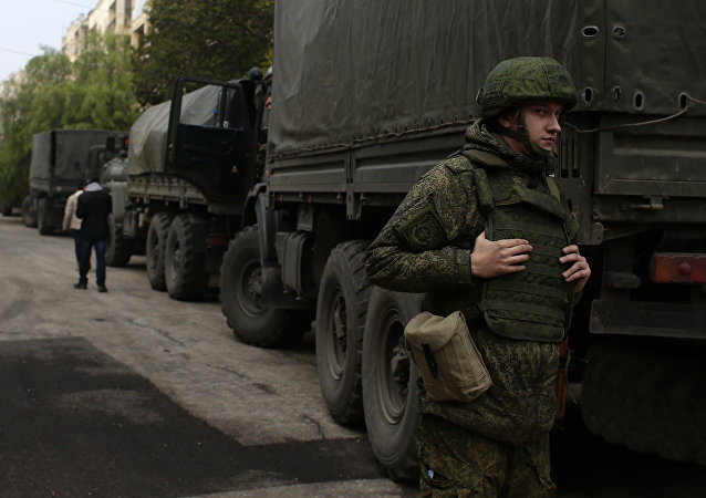 A Russian soldier stands next to an aid convoy in Syria