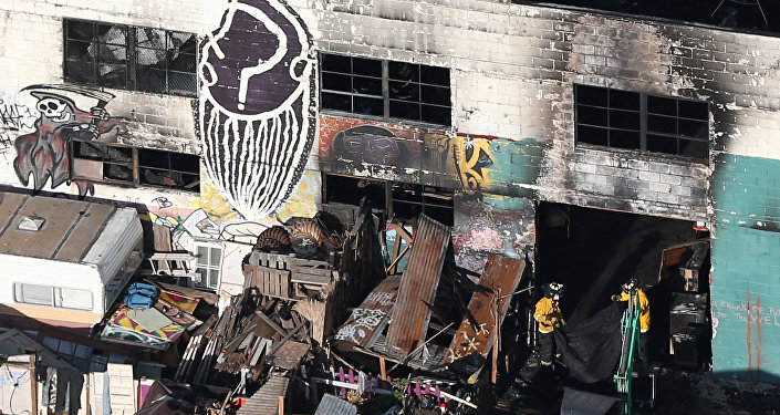 Firefighters work inside the burned warehouse following the fatal fire in the Fruitvale district of Oakland, California, U.S. December 4, 2016
