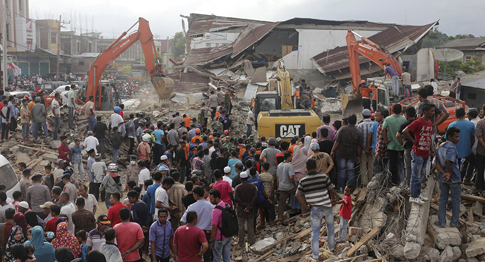 Rescuers use excavators to search for victims under the rubble of collapsed buildings after an earthquake in Pidie Jaya, Aceh province, Indonesia