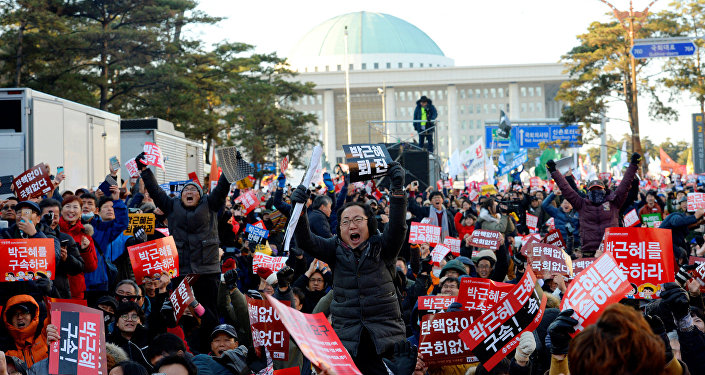 People react after impeachment vote on South Korean President Park Geun-hye was passed, in front of the National Assembly in Seoul, South Korea, December 9, 2016. The sign reads Impeach Park Geun-hye.