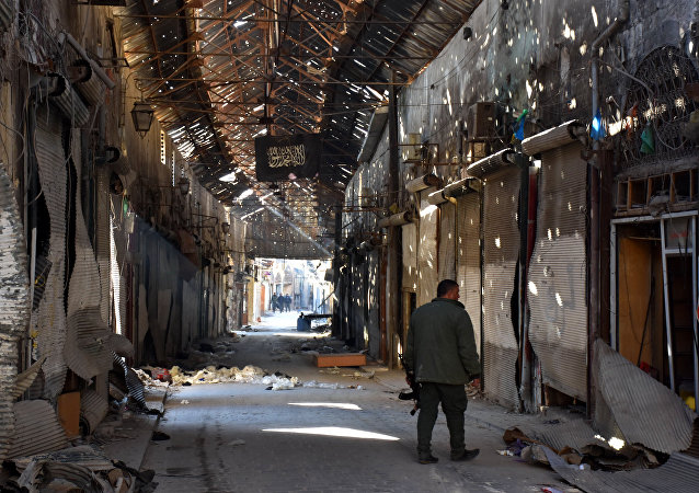 A Syrian Army soldier walks past closed shops in the Bab al-Nasr district of Aleppo's Old City on December 9, 2016