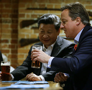 In this Thursday, Oct. 22, 2015 file photo, Britain's Prime Minister David Cameron, right, drinks a pint of beer with Chinese President Xi Jinping, at The Plough pub in Casden, England