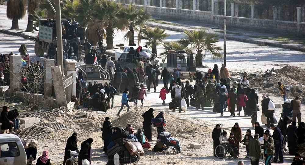Syrian civilians arrive at a checkpoint manned by pro-government forces, at the al-Hawoz street roundabout, after leaving Aleppo's eastern neighbourhoods on December 10, 2016