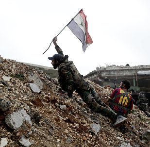 Syrian army soldier places a Syrian national flag during a battle with rebel fighters at the Ramouseh front line, east of Aleppo, Syria