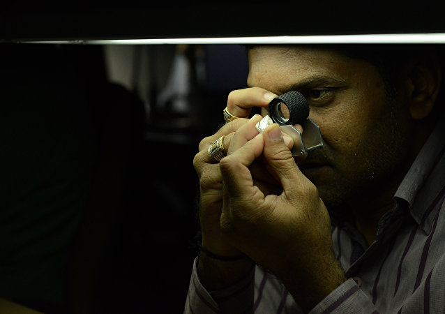 A technician inspects a rough diamond at a manufacturing company in Surat, some 270 kms from Ahmedabad on December 6, 2016