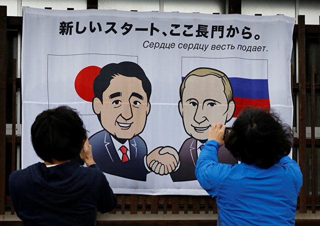 People take photos of a banner showing Japan's Prime Minister Shinzo Abe and Russian President Vladimir Putin at the Senzaki station in Nagato, Yamaguchi prefecture, Japan, December 14, 2016, a day before their summit meeting. The words on top reads, A new start from here in Nagato.