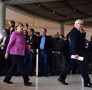 German Chancellor Angela Merkel (R) and Frank-Walter Steinmeier leave after a press conference together with the presidents of the ruling coalition Sigmar Gabriel (SPD)(Unseen) and Horst Seehofer (CSU)(Unseen) to present Frank-Walter Steinmeier as their candidate for German president on November 16, 2016 at the German lower house of parliament (the Bundestag) in Berlin.