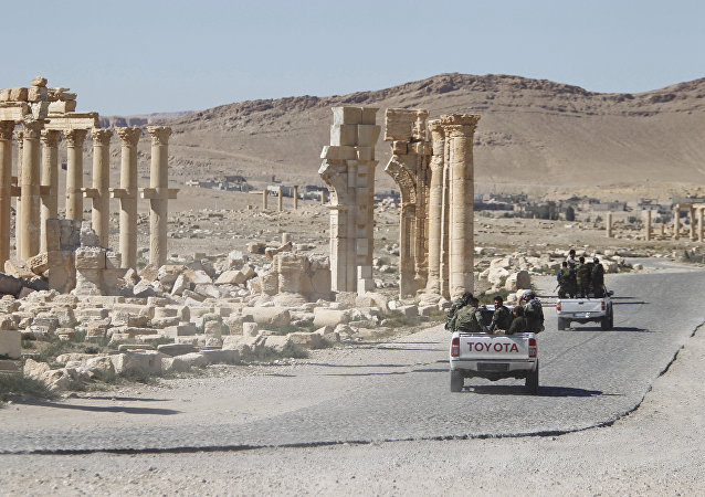 Syrian army soldiers drive past the Arch of Triumph in the historic city of Palmyra, in Homs Governorate, Syria. (File)