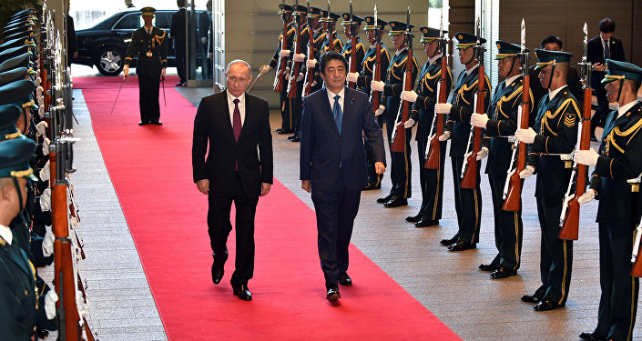 Russian President Vladimir Putin (L) and Japanese Prime Minister Shinzo Abe review an honor guard before their working lunch at Abe's official residence in Tokyo, Japan, December 16, 2016.