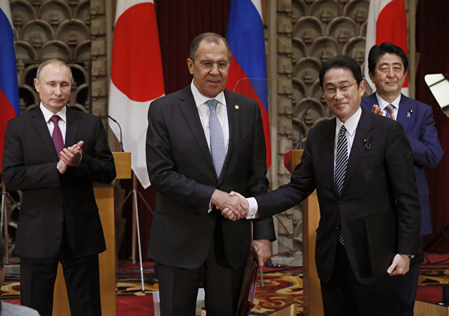 Russian President Vladimir Putin, left, and Japanese Prime Minister Shinzo Abe, rear right, applaud as Russian Foreign Minister Sergey Lavrov, second left, and his Japanese counterpart Fumio Kishida shake hands after exchanging the signed agreement in Tokyo, Japan, Friday, Dec. 16, 2016.