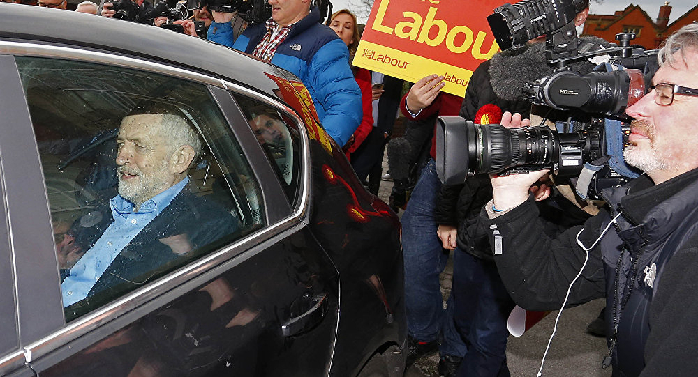 British opposition Labour Party leader Jeremy Corbyn (L) leaves in a car after speaking to the media following Labour candidate Jim McMahon's victory in the by-election for Oldham West and Royton outside Chadderton Town Hall in Chadderton, Oldham, northwest England, on December 4, 2015.