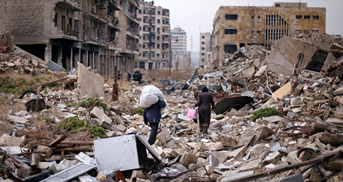 People walk amid the rubble as they carry belongings that they collected from their houses in the government controlled area of Aleppo, Syria December 17, 2016