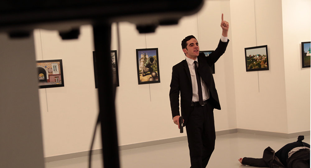 A man gestures near to Andrei Karlov on ground, the Russian Ambassador to Turkey at a photo gallery in Ankara, Turkey, Monday, Dec. 19, 2016