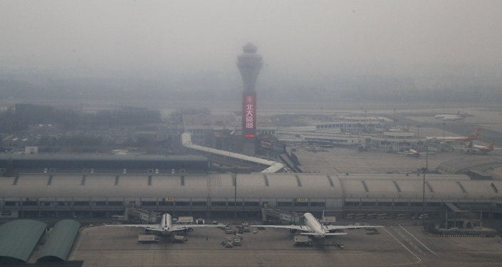 Passenger planes are on the tarmac at the Beijing Capital International Airport shrouded by pollution haze in Beijing, Thursday, Nov. 17, 2016