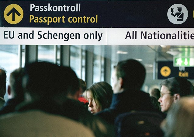 Travellers queue for passport control  (File)