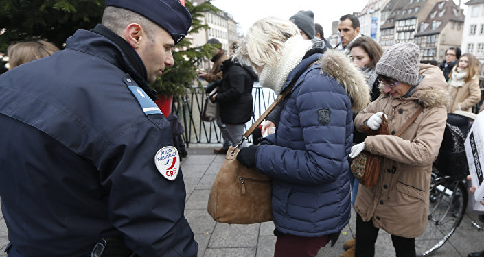People go through security checks before entering the Christmas market in Strasbourg, eastern France, Tuesday the day after a truck ran into a crowded Christmas market and killing people Monday evening in Berlin, Germany