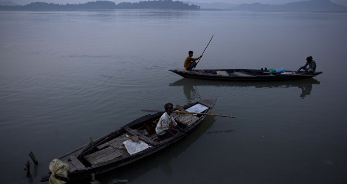 An Indian fisherman paddles a country boat as he leaves for fishing as another man sits in an anchored boat in the river Brahmaputra in Gauhati, India