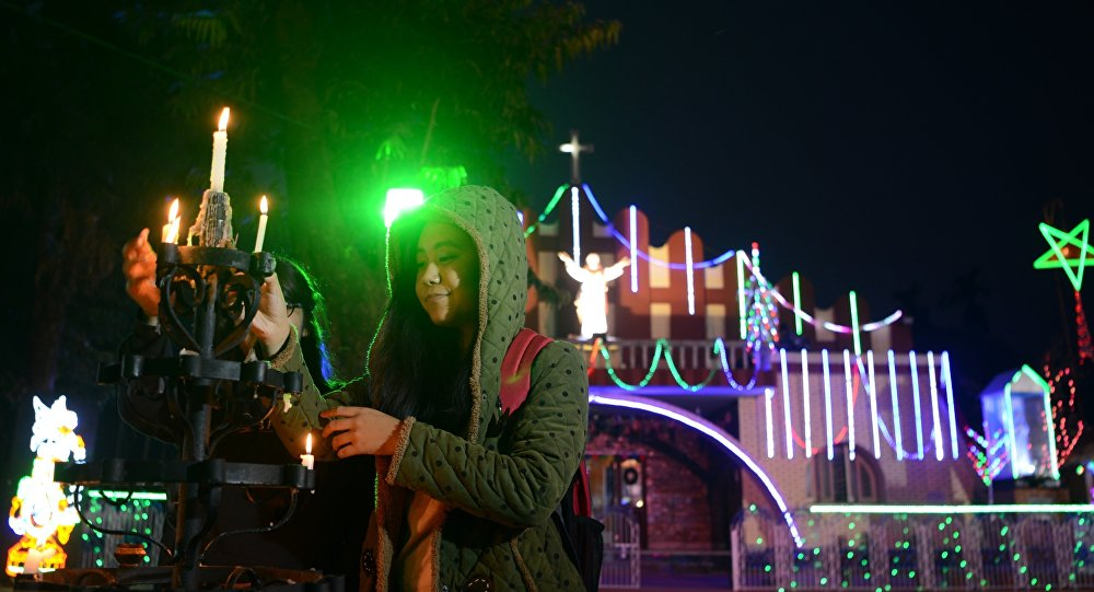 Indian Christians light candles near the illuminated Our Lady Queen Church on Christmas Eve in Siliguri
