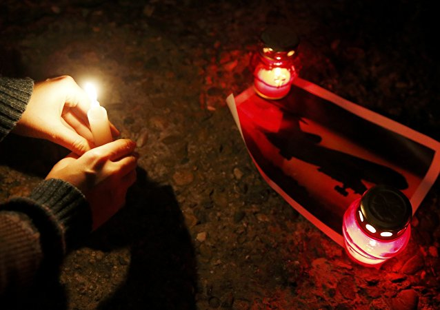 A woman places a candle to honour passengers and crew members of Russian military Tu-154 plane crashed into the Black Sea on its way to Syria on Sunday, at an embankmen in the resort city of Sochi, Russia