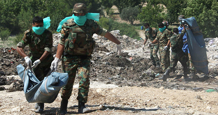 Syrian army troops remove corpses from a  mass grave (File)