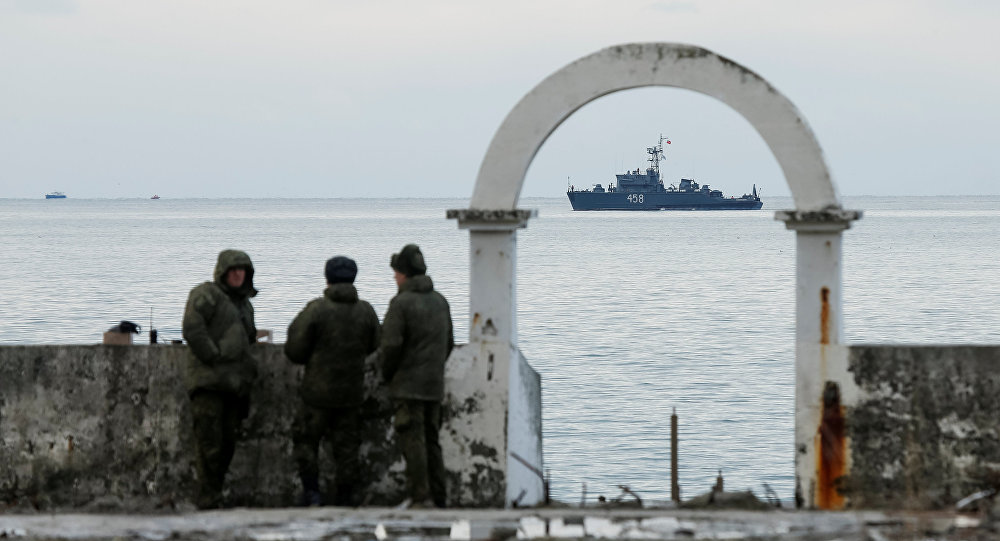 Military personnel watch on a pier as navy ship sails near the crash site of a Russian military Tu-154 plane, which crashed into the Black Sea on its way to Syria on Sunday, in the Black Sea resort city of Sochi, Russia, December 26, 2016