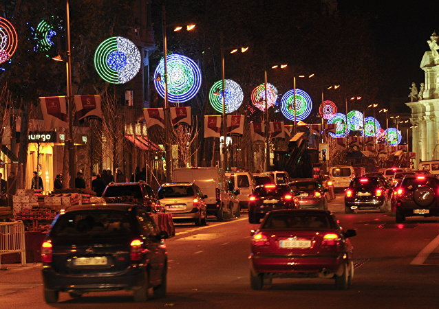 Cars pass next to Christmas lights in a street of Madrid (File)