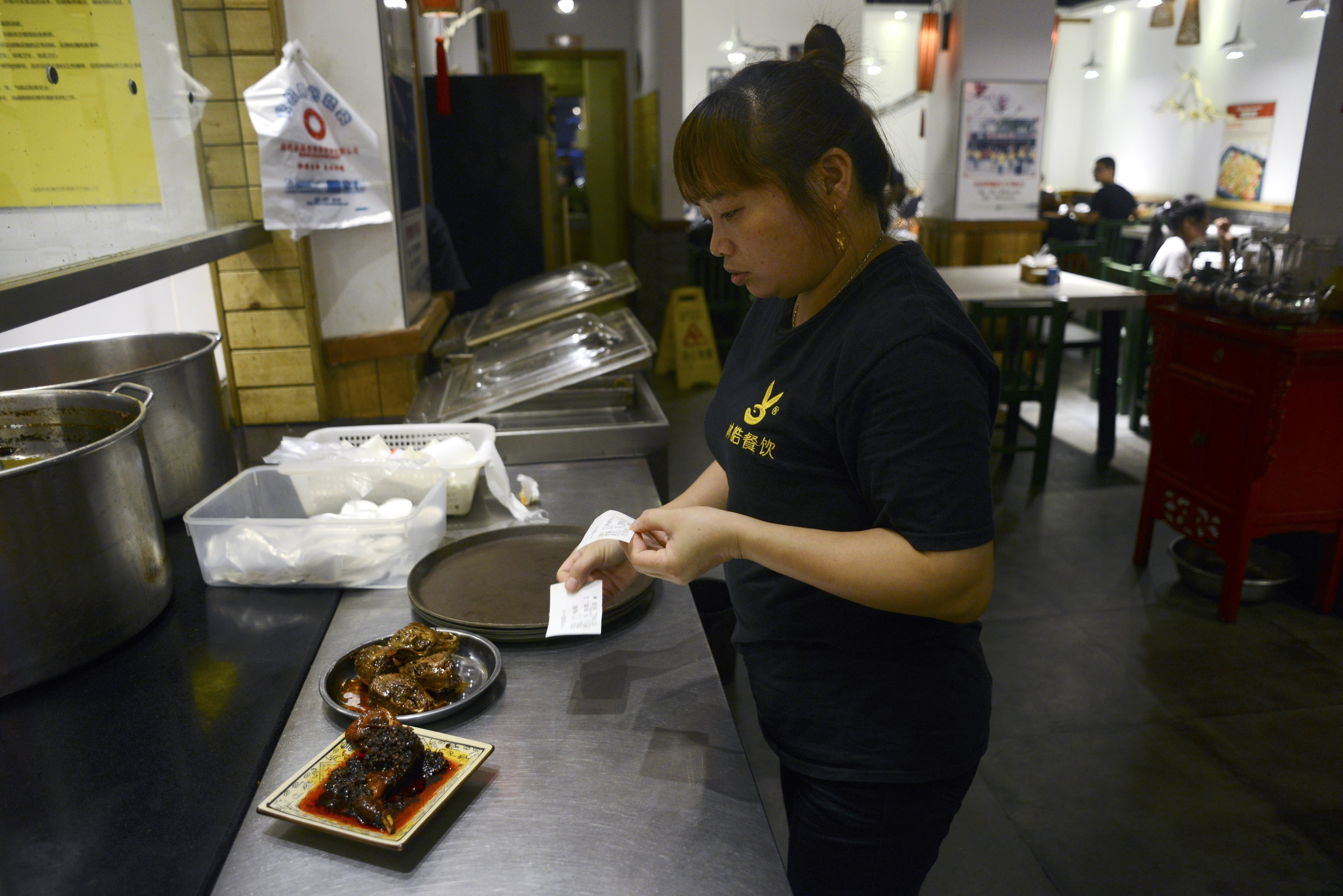 This picture taken on September 8, 2016 shows a waitress preparing a plate of rabbit's head for customers at a restaurant in Chengdu, in southwestern China's Sichuan province