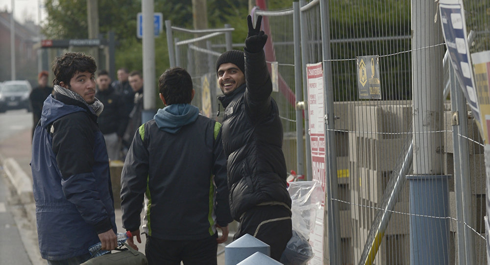 A migrant, who was arrested in Belgium, flashes a victory sign as he crosses the Belgian-French border after being released by the Belgian police at the border on February 26, 2016 in Adinkerke
