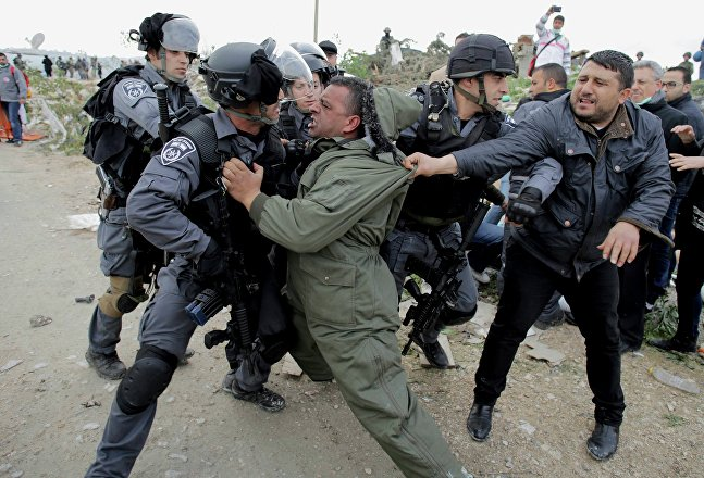 A Palestinian man scuffles with Israeli border policemen as they clear a protest on land that Palestinians said was confiscated by Israel for Jewish settlements, near the West Bank town of Abu Dis near Jerusalem,