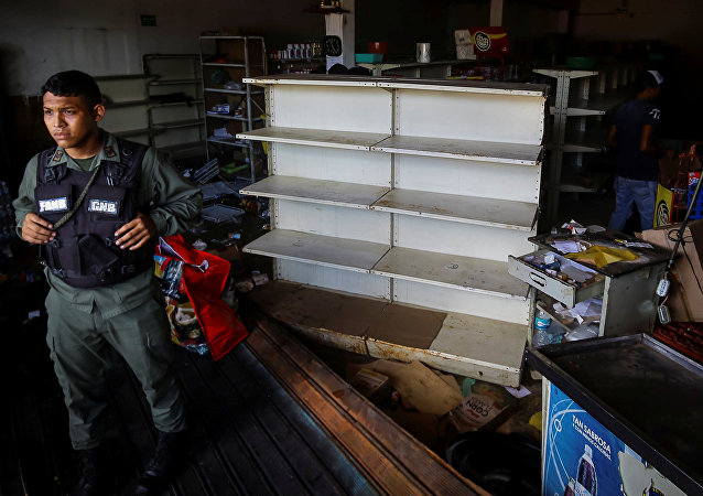 A Venezuelan National Guard stands guard as workers recover the valuables after a supermarket was looted in Ciudad Bolivar