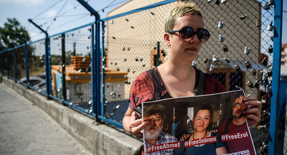 A demostrator holds a placard of Reporters Without Borders Turkey representative Erol Onderoglu, journalist Ahmet Nesin and rights activist and academic Sebnem Korur Fincanci during a demostration in front of the Metris prison on June 24, 2016 in Istanbul