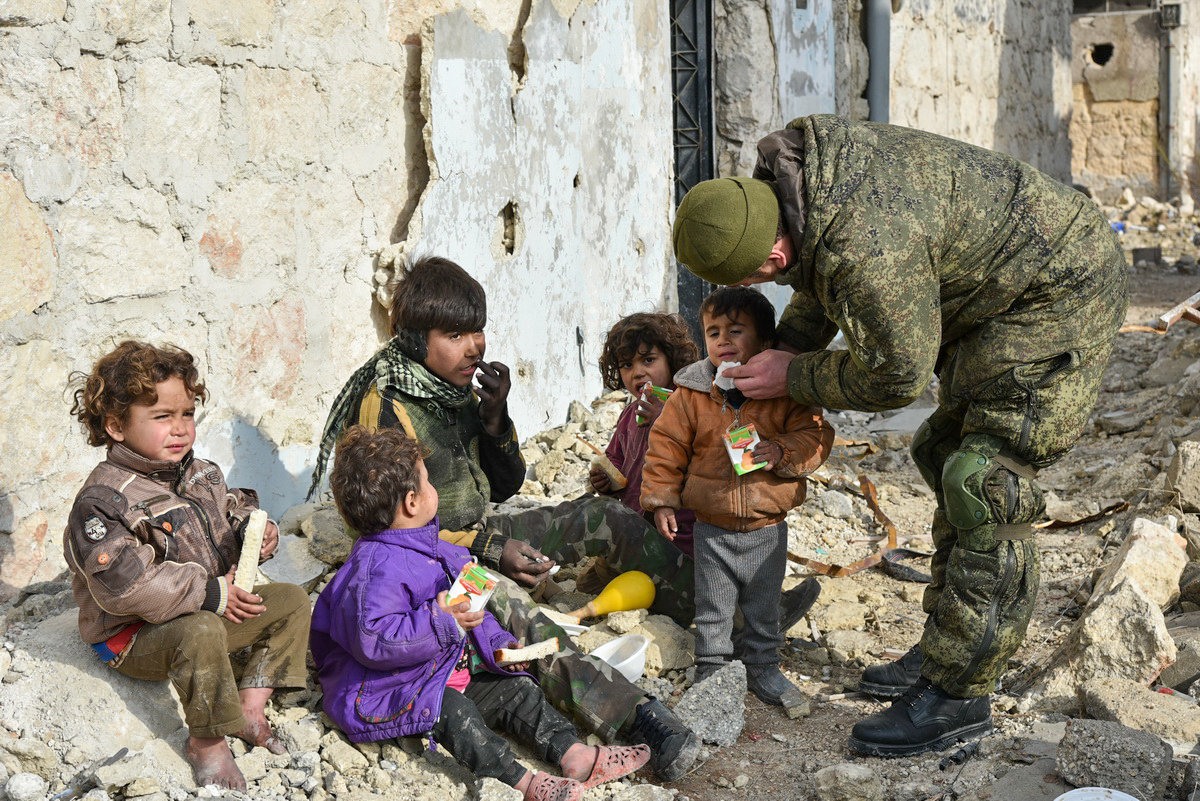 Military engineers of the Russian Army's international counter-mine center are seen in an Aleppo street with children. File photo